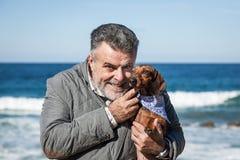 Hombre barbudo atractivo en la playa con el perro basset rojo Fotos de archivo