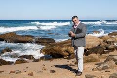Hombre barbudo atractivo en la playa con el teléfono y la tableta Imagen de archivo libre de regalías