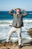 Hombre barbudo atractivo en la playa con las manos en la cabeza Imágenes de archivo libres de regalías