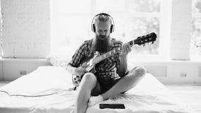 Hombre barbudo atractivo en los auriculares que se sientan en cama que aprende tocar la guitarra usando la tableta en dormitorio  Fotos de archivo
