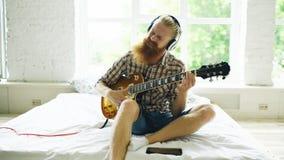 Hombre barbudo atractivo en los auriculares que se sientan en cama que aprende tocar la guitarra usando la tableta en dormitorio  Fotos de archivo libres de regalías