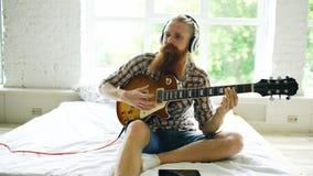 Hombre barbudo atractivo en los auriculares que se sientan en cama que aprende tocar la guitarra usando la tableta en dormitorio  Imagen de archivo