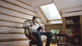 Hombre barbudo atractivo en vidrios que lee un libro y que bebe el café en el ático metrajes