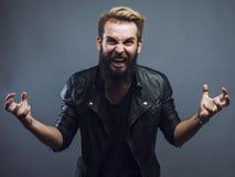 Hombre barbudo atractivo joven del inconformista que gesticula el griterío emocional en estudio Foto de archivo libre de regalías