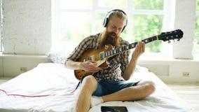 Hombre barbudo atractivo que se sienta en la cama que aprende tocar la guitarra usando la tableta en dormitorio moderno en casa Fotos de archivo libres de regalías