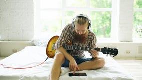 Hombre barbudo atractivo que se sienta en la cama que aprende tocar la guitarra usando la tableta en dormitorio moderno en casa Fotografía de archivo