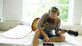 Hombre barbudo atractivo que se sienta en la cama que aprende tocar la guitarra usando la tableta en dormitorio moderno en casa Imagenes de archivo