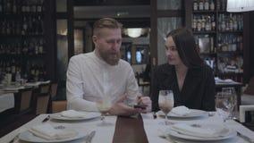 Hombre barbudo atractivo y mujer morena bonita que se sientan en el restaurante en la tabla El hombre muestra a su novia almacen de video