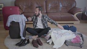 Hombre barbudo cansado del retrato que se sienta en el piso y las maletas que embalan Concepto de preparaci?n para el viaje Ropa almacen de video