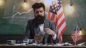 Hombre barbudo con el dinero del dólar para el soborno Reforma americana de la educación en la escuela en el 4 de julio Planeamie metrajes