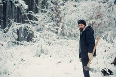 Hombre barbudo con el hacha en bosque nevoso imagenes de archivo