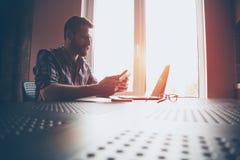 Hombre barbudo con el ordenador portátil y la tableta digital Imágenes de archivo libres de regalías