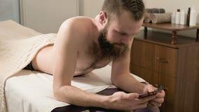 Hombre barbudo con el pelo trenzado que miente en el sofá médico para un tipo mensaje del masaje de SMS en su smartphone en la of almacen de video