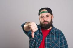 Hombre barbudo con la gorra de béisbol con el pulgar abajo Fotografía de archivo