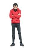 Hombre barbudo con los brazos cruzados en la sudadera con capucha roja que mira abajo Imágenes de archivo libres de regalías
