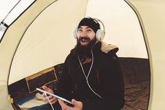 Hombre barbudo con película y risa del reloj de la tableta Foto de archivo libre de regalías