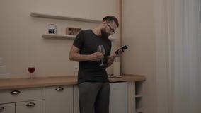 Hombre barbudo con smartphone y la copa de vino almacen de metraje de vídeo