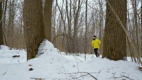 Hombre barbudo de los deportes en la capa amarilla que corre en bosque en día de invierno frío metrajes