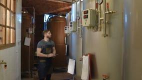 Hombre barbudo del cervecero en un fondo de los tanques de la cerveza y una cervecería que hace notas en una tableta metrajes