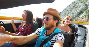 Hombre barbudo del inconformista con el sombrero que conduce en la autopista de la montaña con los amigos almacen de metraje de vídeo