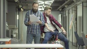 Hombre barbudo del retrato que estudia los papeles en la oficina Colega joven que monta la bici en la oficina y el individuo barb almacen de metraje de vídeo