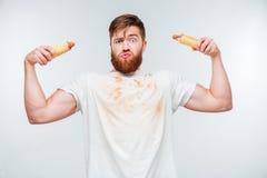 Hombre barbudo divertido en la camisa asquerosa que se sostiene a los perritos calientes fotografía de archivo libre de regalías