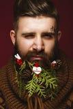 Hombre barbudo divertido en una imagen del ` s del Año Nuevo como Santa Claus con las decoraciones en su barba Banquete de la Nav Imágenes de archivo libres de regalías