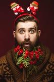 Hombre barbudo divertido en una imagen del ` s del Año Nuevo como Santa Claus con las decoraciones en su barba Banquete de la Nav Fotografía de archivo libre de regalías