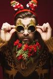 Hombre barbudo divertido en una imagen del ` s del Año Nuevo como Santa Claus con las decoraciones en su barba Banquete de la Nav Foto de archivo libre de regalías