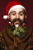 Hombre barbudo divertido en una imagen del ` s del Año Nuevo como Santa Claus con las decoraciones en su barba Banquete de la Nav Foto de archivo