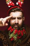 Hombre barbudo divertido en una imagen del ` s del Año Nuevo como Santa Claus con las decoraciones en su barba Banquete de la Nav Imagenes de archivo