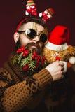 Hombre barbudo divertido en una imagen del ` s del Año Nuevo como Santa Claus con las decoraciones en su barba Banquete de la Nav Imagen de archivo