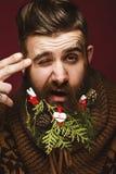Hombre barbudo divertido en una imagen del ` s del Año Nuevo como Santa Claus con las decoraciones en su barba Banquete de la Nav Fotos de archivo libres de regalías