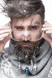 Hombre barbudo divertido en una imagen del ` s del Año Nuevo con nieve y decoraciones en su barba Banquete de la Navidad Foto de archivo libre de regalías