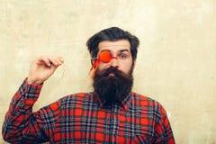 Hombre barbudo divertido que lleva a cabo el corazón rojo en el palillo antes de ojo fotografía de archivo