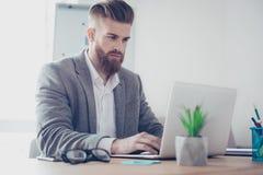 Hombre barbudo elegante concentrado hermoso en chaqueta usando su la foto de archivo