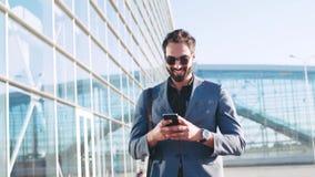 Hombre barbudo elegante en gafas de sol usando el dispositivo mientras que pasa por el terminal de aeropuerto, sonrisas al texto