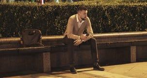 Hombre barbudo elegante que se sienta en banco en parque en la noche y que mira en teléfono móvil almacen de video