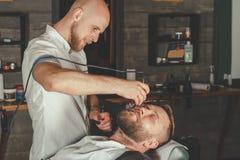 Hombre barbudo en barbería Imagen de archivo