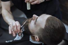 Hombre barbudo en barbería Fotos de archivo
