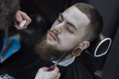 Hombre barbudo en barbería Fotografía de archivo
