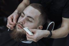 Hombre barbudo en barbería Foto de archivo