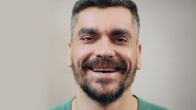 Hombre barbudo en buen humor que ríe caluroso, primer de la cara, emociones positivas metrajes