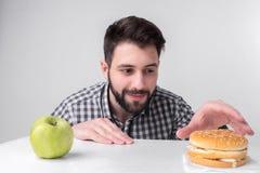 Hombre barbudo en camisa a cuadros en un fondo ligero que sostiene una hamburguesa y una manzana El individuo toma la decisión en Foto de archivo libre de regalías