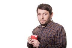 Hombre barbudo en camisa de tela escocesa con la taza roja en sus manos Aislado en el fondo blanco Fotos de archivo