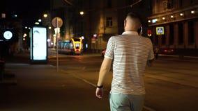 Hombre barbudo en camiseta blanca y negra rayada y pantalones cortos verdes que caminan en la calle en la noche y la charla por e almacen de metraje de vídeo