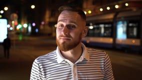 Hombre barbudo en camiseta rayada del polo en la mirada de la calle de la noche correcta que para arriba almacen de video