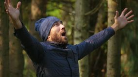 Hombre barbudo en chaqueta y sombrero hecho punto aumentando sus manos para arriba que gritan en alta voz celebre activamente el  almacen de video