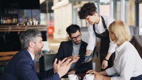 Hombre barbudo en el traje que hace el pago en línea en café entonces que habla con los compañeros de trabajo almacen de video