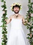 Hombre barbudo en el vestido de la boda de una mujer en su cuerpo desnudo, aferrándose en la vid el hacer muecas y divertido en s Imagen de archivo
